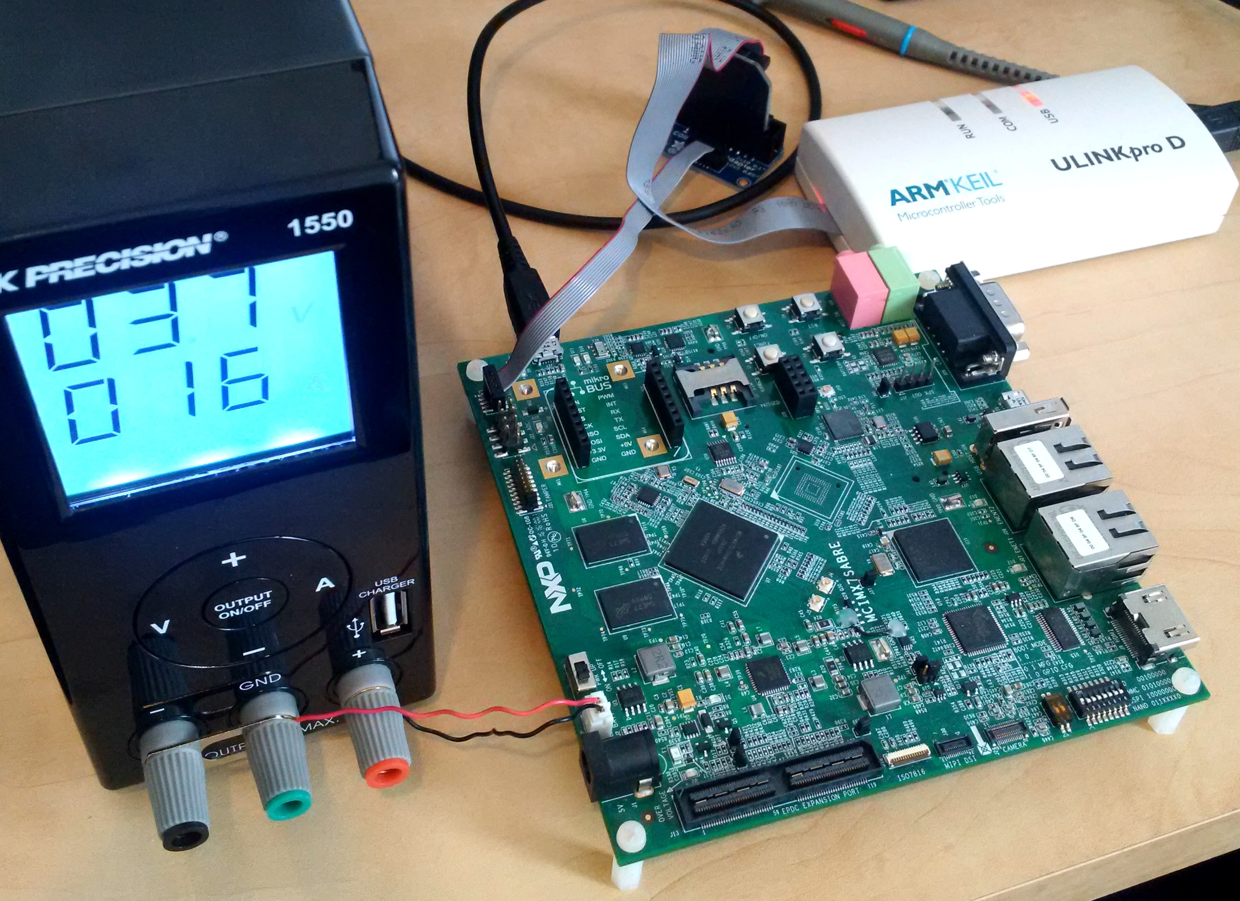 i.MX7D Sabre with debug probe and bench top lab power supply connected.